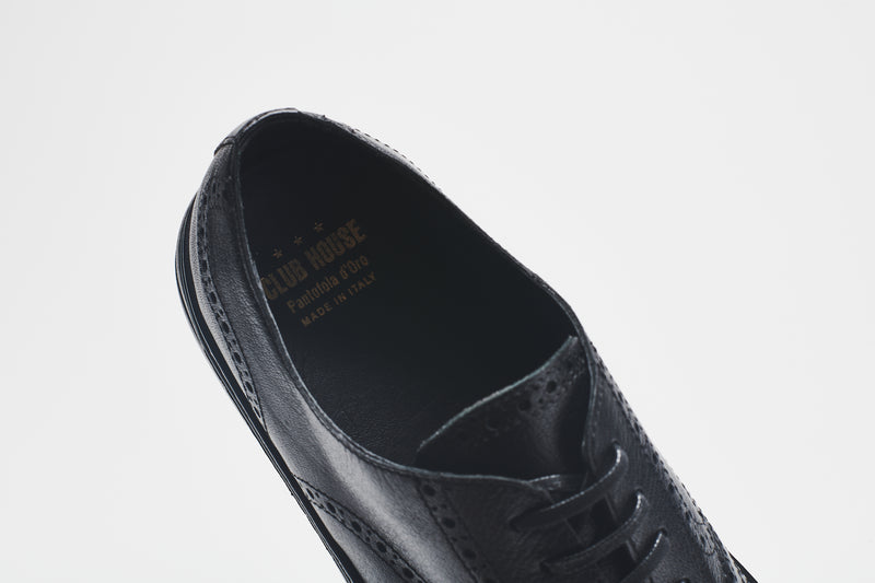 The heel lining of a chunky leather men's shoe in premium black leather, set on black soles, with black laces