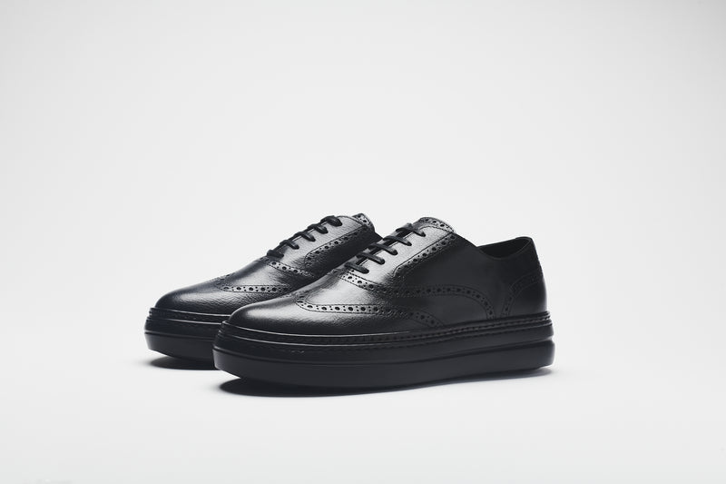 A chunky leather men's shoe in premium black leather, set on black soles, with black laces