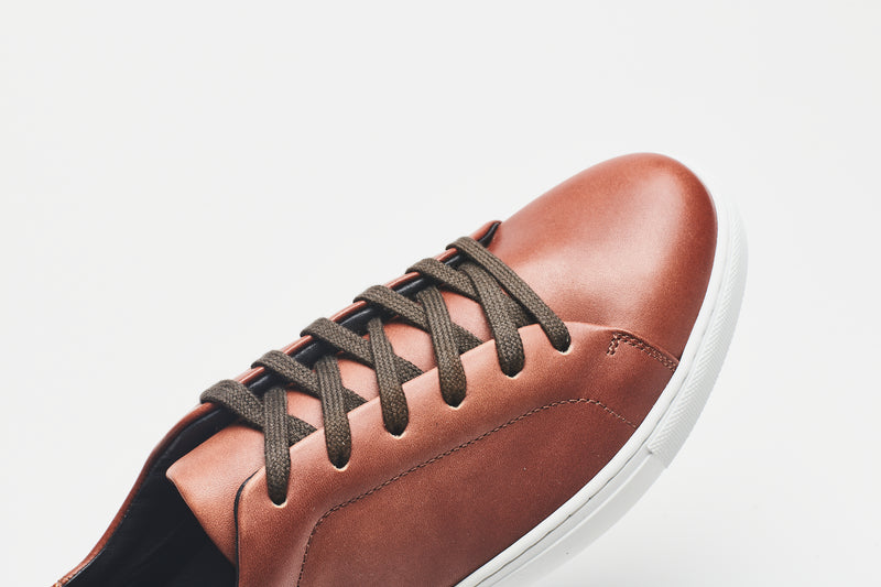 Dark brown laces on a mid-brown men's leather shoe with a white sole