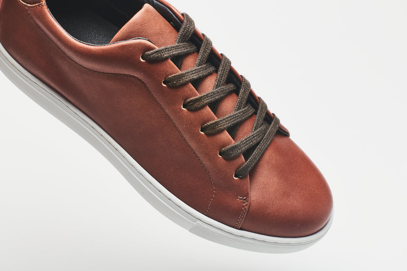 Dark brown laces on a mid-brown men's leather shoe, with a white sole and rounded toe