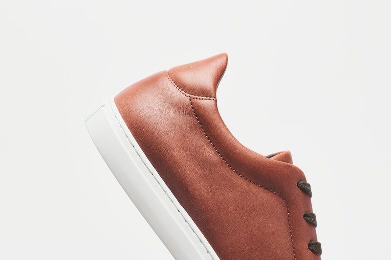 The heel section of a men's brown leather sneaker with a white sole