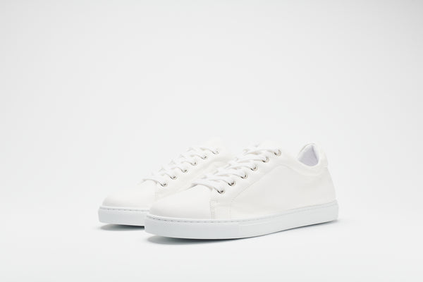 A men's white leather sneaker with a white sole and white laces
