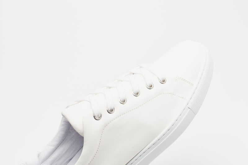 A close-up of a men's white leather sneaker with a white sole and white laces
