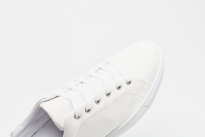A men's white leather sneaker with a white inner sole and white laces