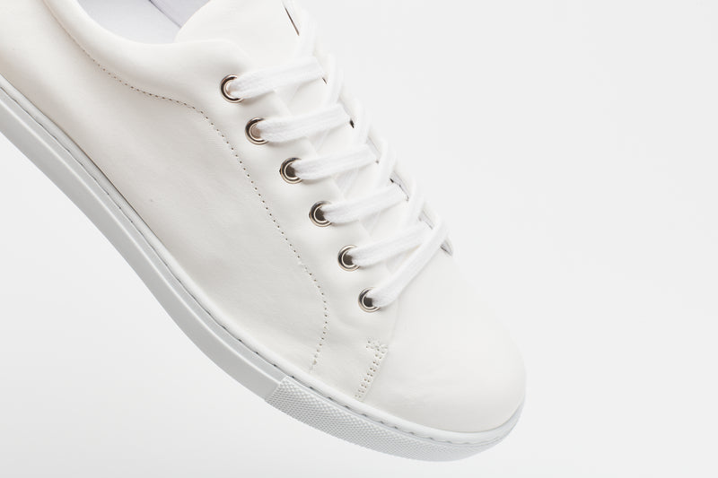 White laces on a men's white leather sneaker with a white sole