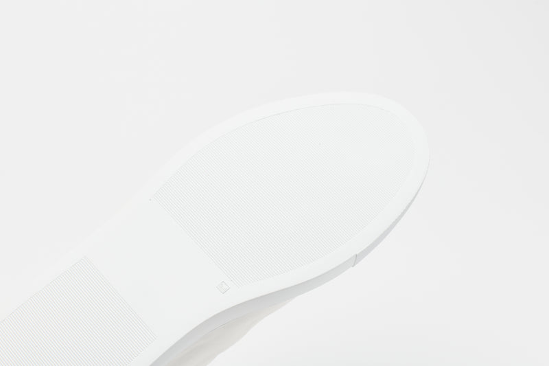 The sole of a men's white leather sneaker with grooves to enable flexibility