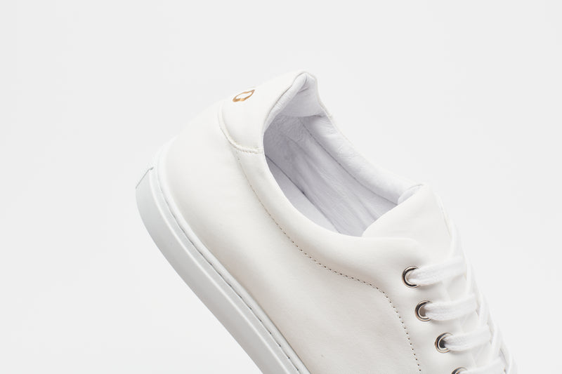 The heel section of a men's white leather sneaker with a white lining, white laces and white sole