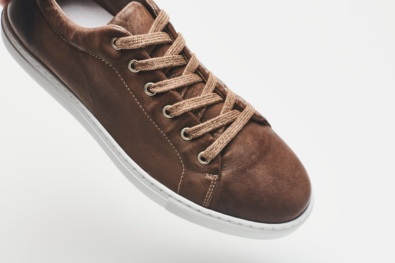 Mid-brown laces on a dark brown men's leather shoe