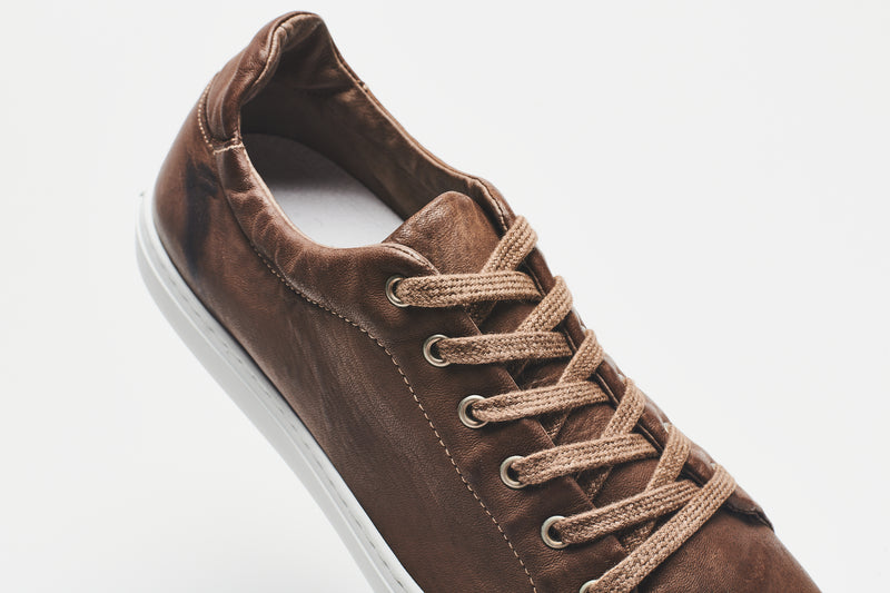 The white lining of a men's dark brown leather shoe, with a white sole and mid-brown laces