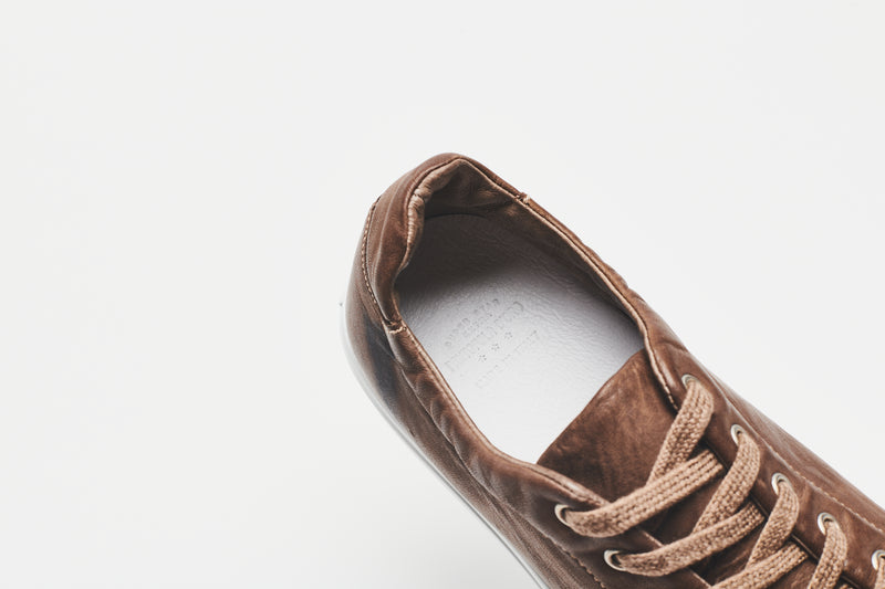 A close-up of the white lining inside a men's brown leather shoe