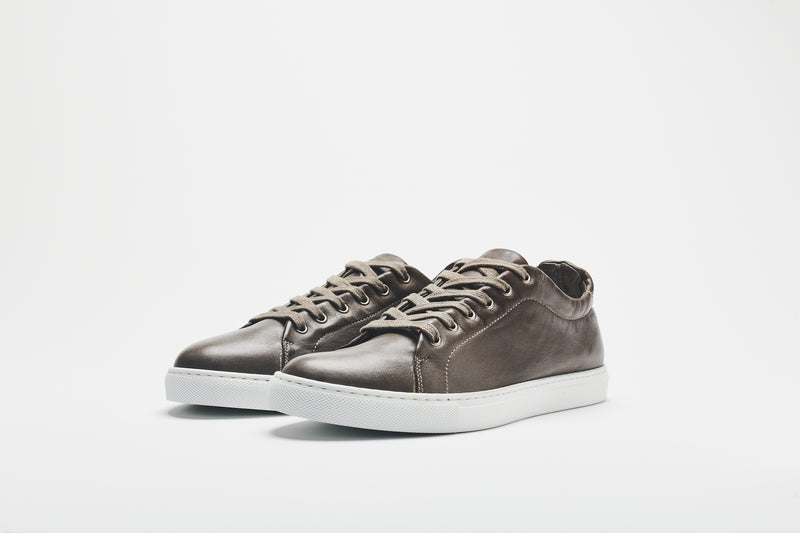 A grey-brown men's leather sneaker on a white sole