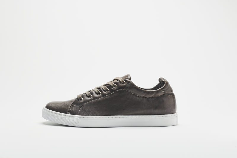 A side image of a grey-brown men's leather sneaker on a white sole