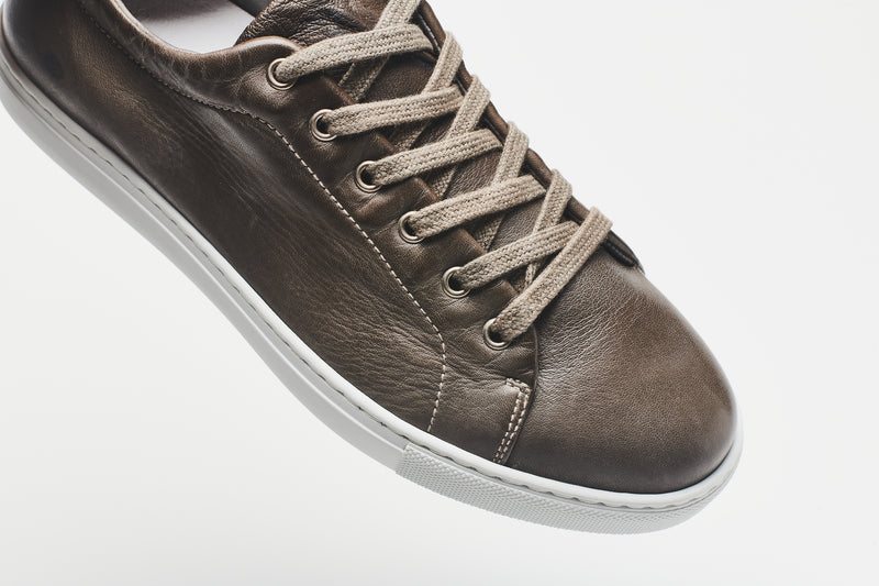 Light grey-brown laces on a darker grey-brown men's leather sneaker