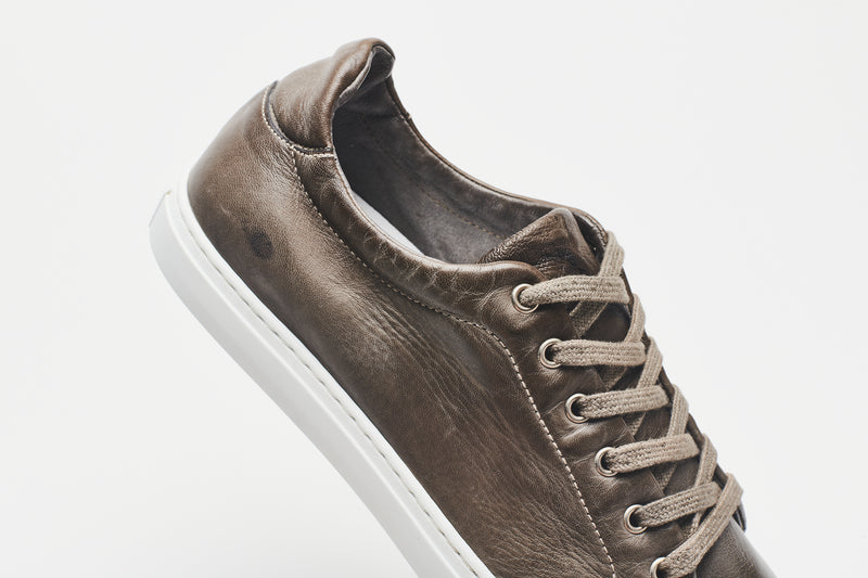 A side image of a men's leather sneaker in grey-brown with a white sole