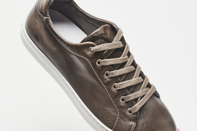 The white lining of a men's grey-brown leather sneaker