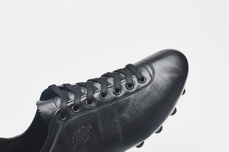 Black laces on a men's black leather football boot