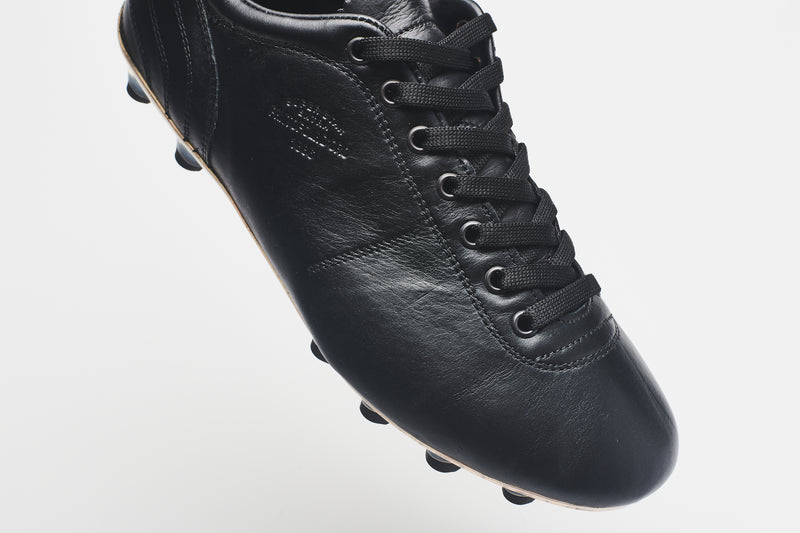 The side of a men's black leather football boot