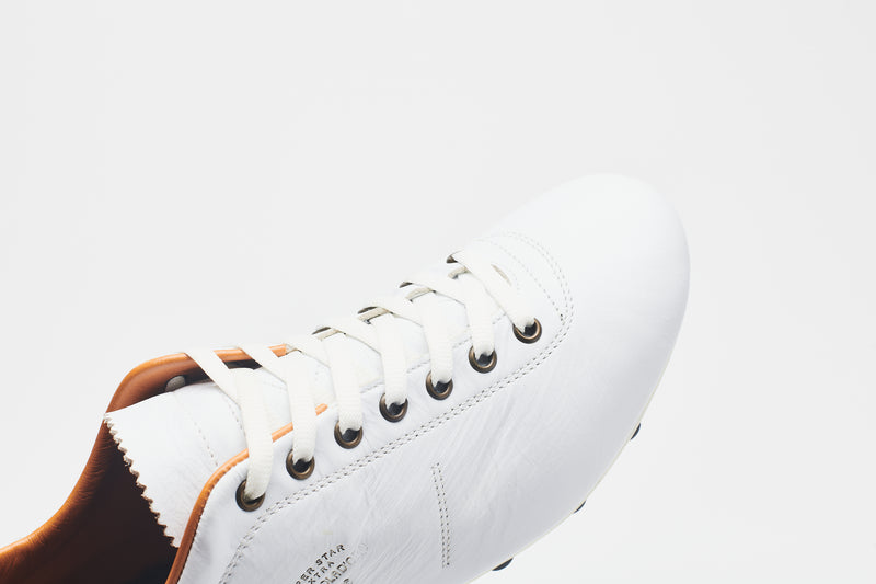White laces on a men's all-white leather football boot with a tan lining