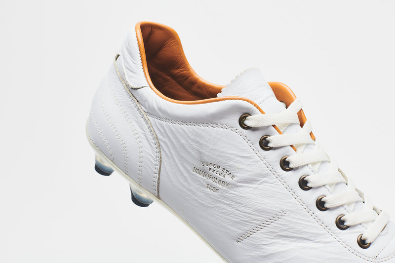 The tan lining of a men's all-white leather football boot