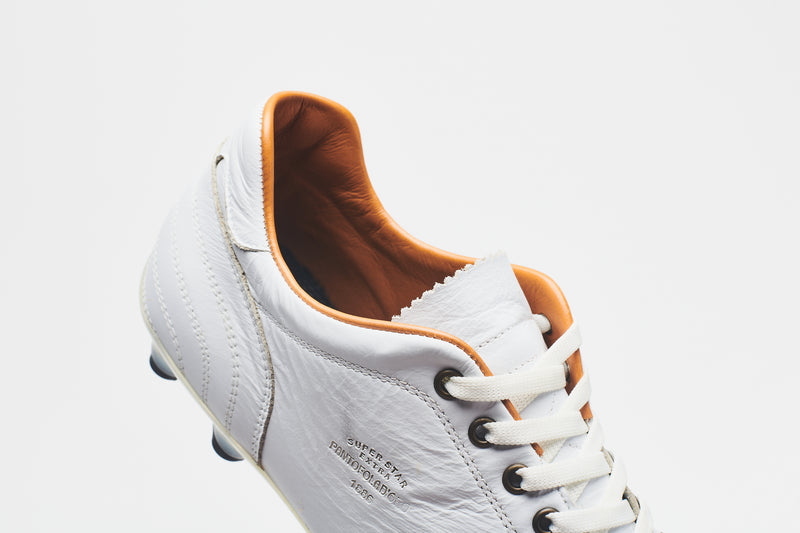 The tan lining and white laces on a men's all-white leather football boot