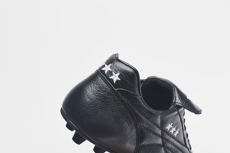 Three gold stars on the heel tab of a men's all-black football boot