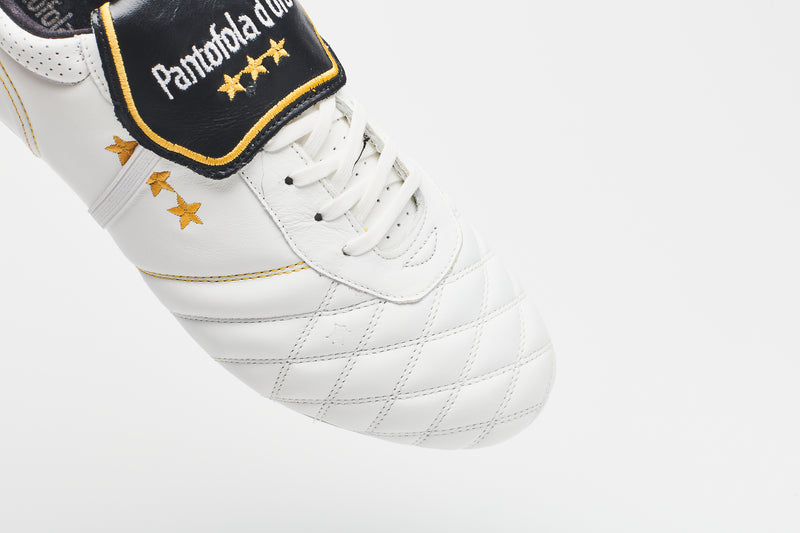 The gold logo on the tongue of a men's white leather football boot