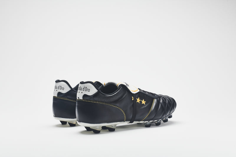 The white heel tab of a men's football boot in black quilted leather with gold logo detailing
