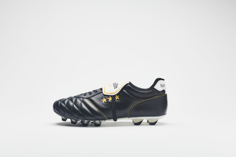 A side image of a men's football boot in black quilted leather with a white tongue, gold logo detail, and black-tipped studs