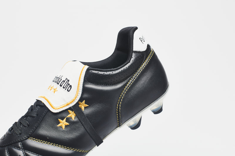 A side close-up image of a men's leather football boot in black leather with gold logo detailing and a white tongue