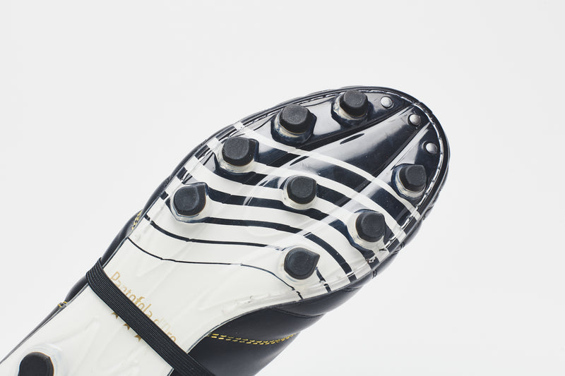 The white sole of a black men's leather football boot, with black wave-graphic design for detail and style