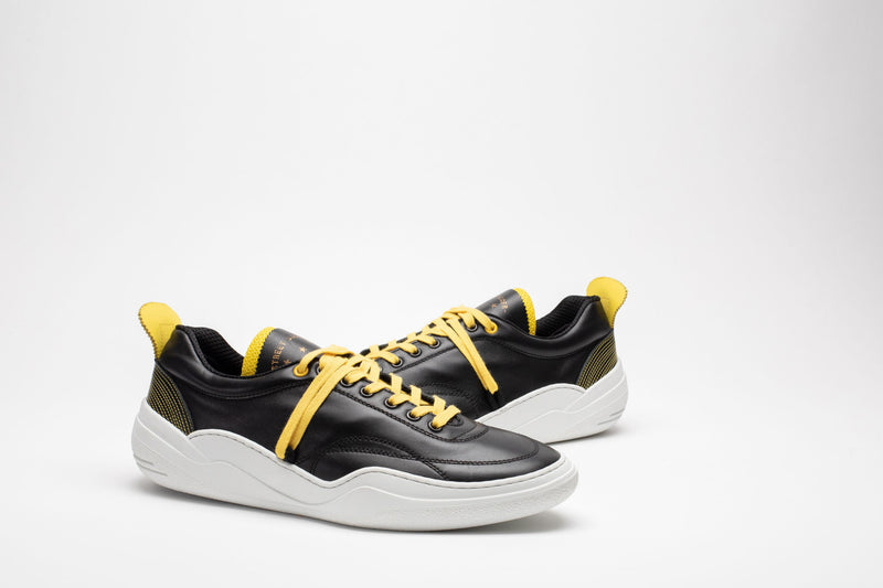Styled image of men's leather trainers in black, yellow and white