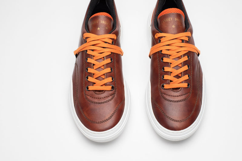 Aerial image of men's leather trainers in brown, orange and white