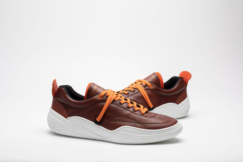 Styled image of men's leather trainers in brown, orange and white