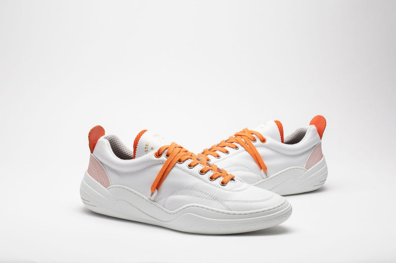 Styled image of men's leather trainers in orange and white