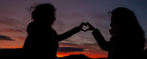 two sillhouettes of people making a heart with their hands at dusk with a beautiful sunset