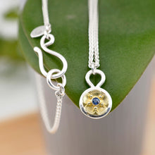 "Load image into Gallery viewer, The Beacon of Hope necklace depicts a single glistening forget-me-not flower, symbolizing light, hope, and enduring love. This necklace is handcrafted using your choice of tarnish resistant sterling silver and/or solid 18K yellow gold, 18"" argentium silver wheat chain & a Ceylon blue sapphire. Chloe Leigh Designs: Handcrafted Fine Jewelry"