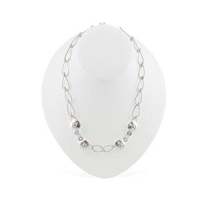 This Bella Necklace is draped over a white mannequin. It is a hand-wrought teardrop chain with four circular balls positioned at the  front of the necklace.