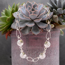 Load image into Gallery viewer, This Bella Necklace is draped around a green and purple succulent plant. It is a hand-wrought teardrop chain with four circular balls positioned at the  front of the necklace.