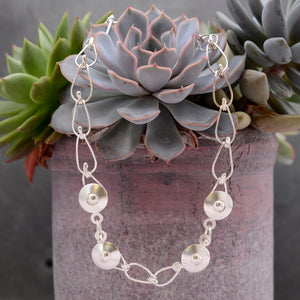 This Bella Necklace is draped around a green and purple succulent plant. It is a hand-wrought teardrop chain with four circular balls positioned at the  front of the necklace.