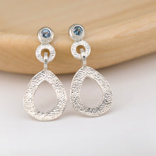 Load image into Gallery viewer, These hand-textured dangle post earrings features 3mm blue Montana sapphires. These earrings are positioned on a light stained wood.
