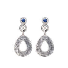 Load image into Gallery viewer, These hand-textured silver dangle post earrings features 3mm brilliant Ceylon blue sapphires. These teardrop dangles have a wider base to make a statement.