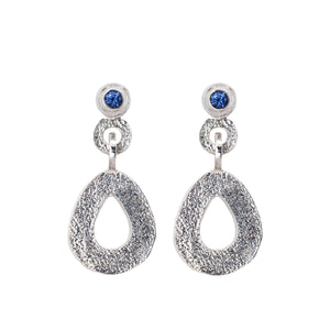 These hand-textured silver dangle post earrings features 3mm brilliant Ceylon blue sapphires. These teardrop dangles have a wider base to make a statement.