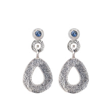 Load image into Gallery viewer, These hand-textured silver dangle post earrings features 3mm ocean blue Montana sapphires. These teardrop dangles have a wider base to make a statement.