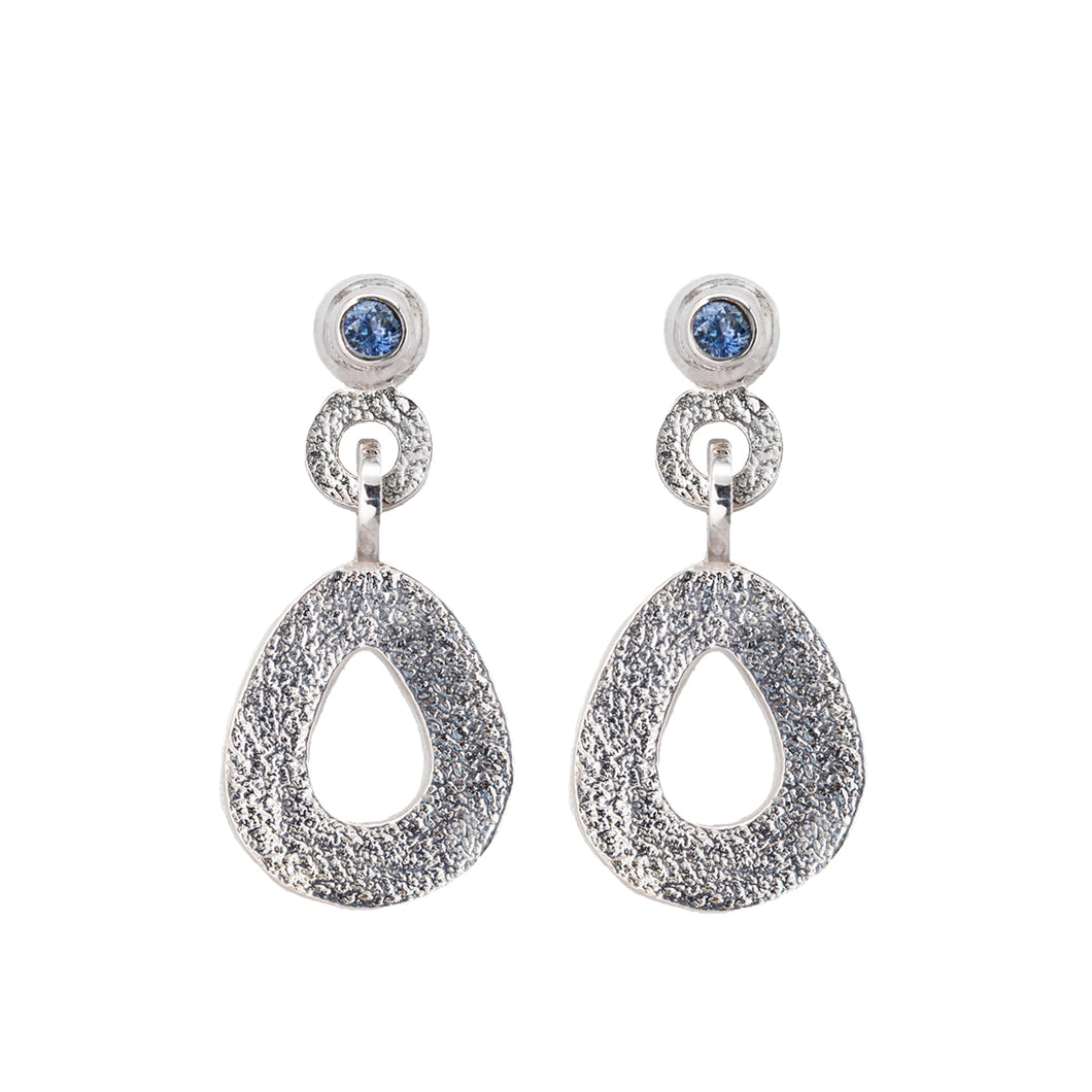 These hand-textured silver dangle post earrings features 3mm ocean blue Montana sapphires. These teardrop dangles have a wider base to make a statement.