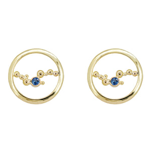 These stud earrings are handcrafted with solid 18K yellow gold, & a single 3mm Ceylon blue sapphire embraced in the middle of an abstract array of gold granulation. Against a white background.