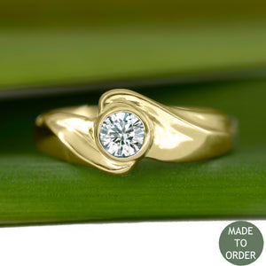 This ring, Timeless, embodies the elegance and harmony of the sea. This is a timeless solitaire ring with a unique flare. The diamond is encircled by a graceful wave in 18K Yellow Gold. The band is finished with a high polish.  Edit alt text
