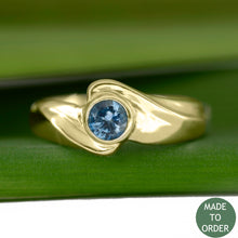 Load image into Gallery viewer, This ring, Timeless, embodies the elegance and harmony of the sea. This is a timeless solitaire ring with a unique flare. The ocean blue Montana sapphire is encircled by a graceful wave in 18K Yellow Gold.  The band is finished with a high polish.