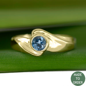 This ring, Timeless, embodies the elegance and harmony of the sea. This is a timeless solitaire ring with a unique flare. The ocean blue Montana sapphire is encircled by a graceful wave in 18K Yellow Gold.  The band is finished with a high polish.