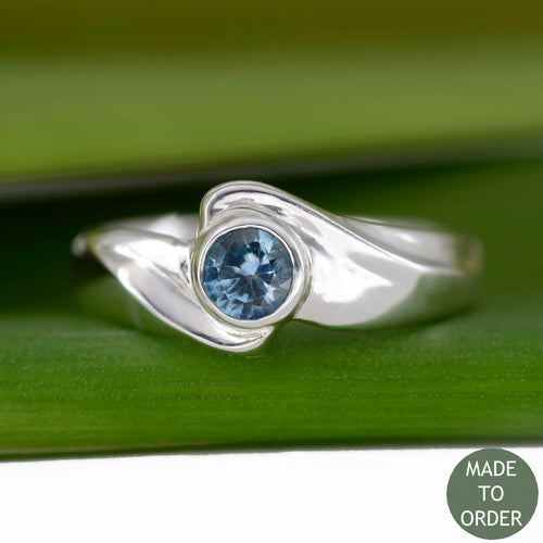 This ring, Timeless, embodies the elegance and harmony of the sea. This is a timeless solitaire ring with a unique flare. The ocean blue Montana sapphire is encircled by a graceful wave in Silver.  The band is finished with a high polish.