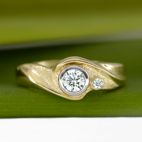 This ring, Embrace, embodies the romance of the sea. The diamonds are caressed by wave formations sculpted in 18K Yellow Gold. Around the gemstone, the metal is hand-textured creating a sparkling sand-like finish. The band is finished with a high polish.